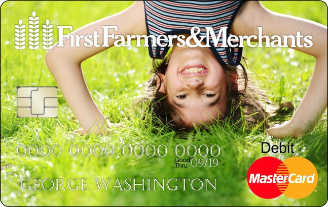 a debit card with a custom photo of a child standing on their head in the grass