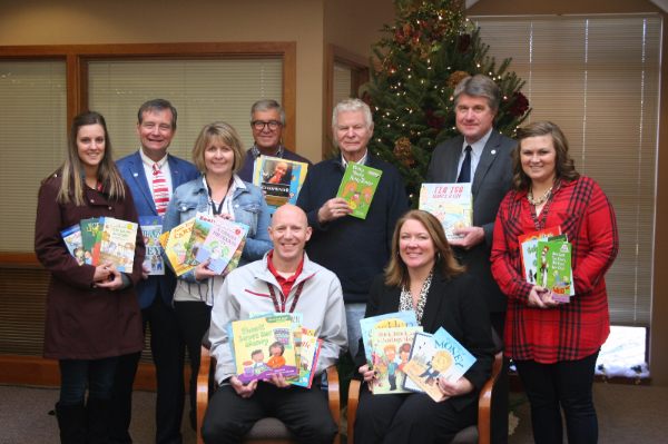Cannon Falls Advisory Board and Cannon Falls teachers receiving books on financial education.